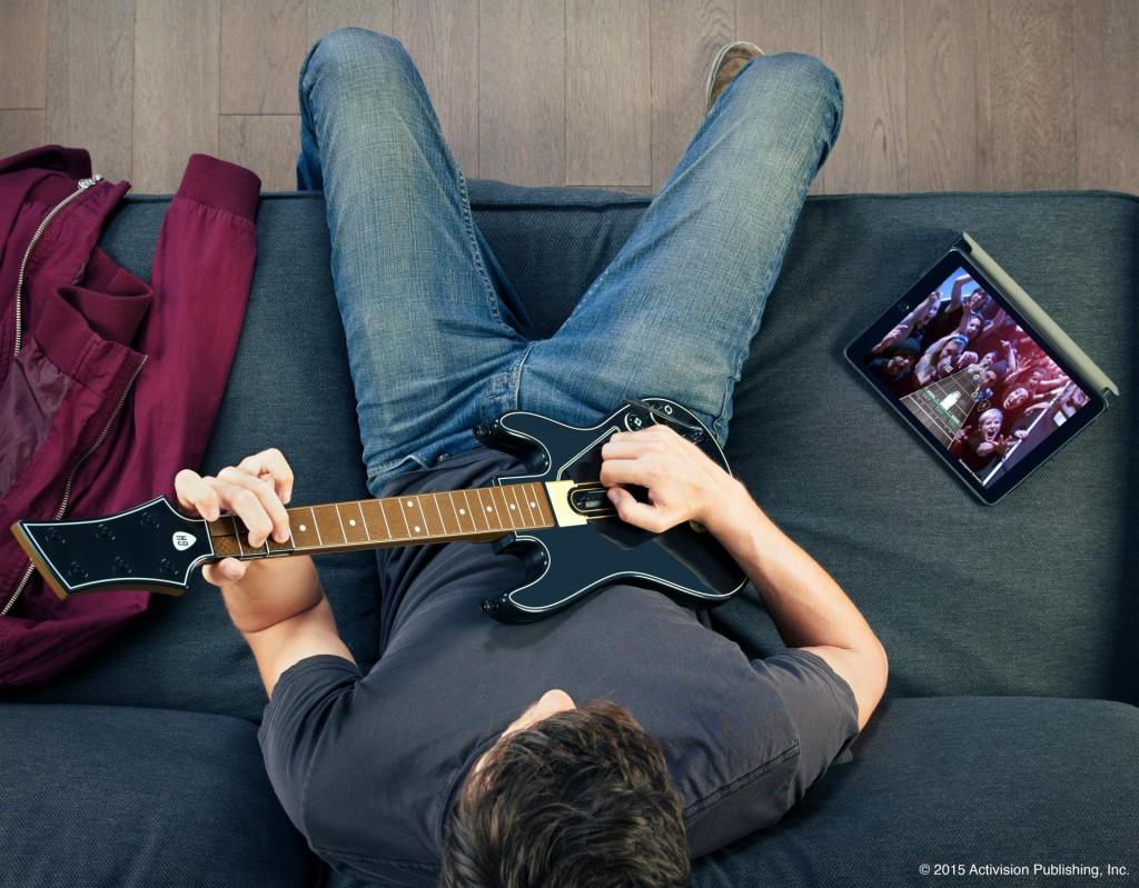 Older teen playing Guitar Hero Live in the Livingroom.